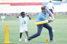 Howzat Harry! The prince whacks a ball out to the boundary as a fielder looks on at the Si...