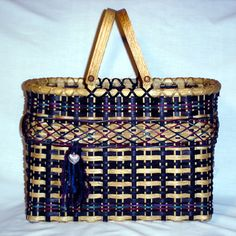 """CRISS CROSS SWING HANDLE It has a woven base and double sets of spokes to make it very sturdy to carry heavy items or all your yarn and quilt squares.  The basic color is black but accented with burgundy, teal and purple reed and yarn.  Yarn and heart embellishment are included in kit.  The majority of weaving is start/stop weaving and near the top is criss cross French randing.  The swing handle inserts make it a great carrying basket. Height w/o handles 11-1/2"""", Width  9"""", Length  17"""""""