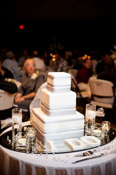gray and white three tier square wedding cakes- maybe with Navy incorporated and flowers only on the top?