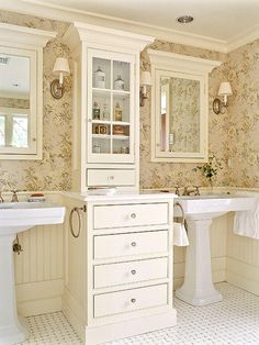 A custom cabinet between two pedestal sinks means you can have the style of a pedestal along with the function of a vanity. A shallow upper cabinet offers counter space. Recessed medicine cabinets above the sinks supplement storage.