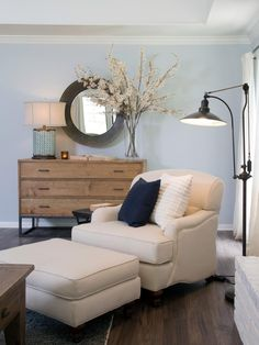 As seen on HGTV's Fixer Upper, a comfy armchair is adorned with a navy throw pillows and sits in the newly renovated living room of the Gaspar home. A dresser becomes a storage space topped with a lamp and decorative flowers. A round mirror is placed above the dresser.