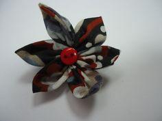 Jolie barrette en coton dans les tons noir, beige, rouge, bleu et blanc, en forme de fleur, avec un coeur en bouton rouge. La barrette est une pince crocodile de 3.3 cm