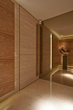 Revestimento da parede do hall em espelho bronze colado sobre MDF com rodapé em aço inox