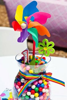1st birthday gumballs in vase centerpiece. Pinwheels, and #1 candle on top. Rainbow Party