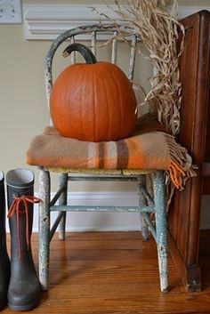 Love the combination of a throw, cornhusks, and the perfect pumpkin adorning a prim chair!