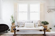 white living room, white throw pillows, mudcloth pillow, ivory shutters, off white, pantone coconut milk, ivory