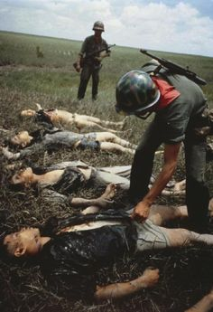 A South Vietnamese Ranger searches the bodies of Viet Cong soldiers who were killed in a government operation against the Communist guerrillas in the Mekong Delta area (40 miles south west of Saigon), 4 October 1964.
