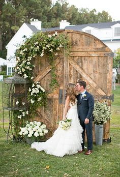 Brides.com: . This couple re-purposed an old barn door to create a stunning ceremony backdrop dressed with white roses and fresh greenery.