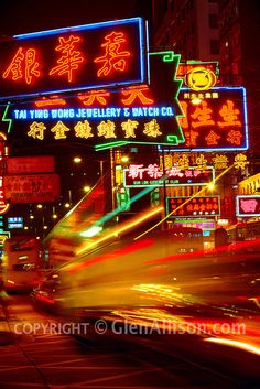 China, Hong Kong, Kowloon, night-lit street scene with time-exposed tailights and neon signs