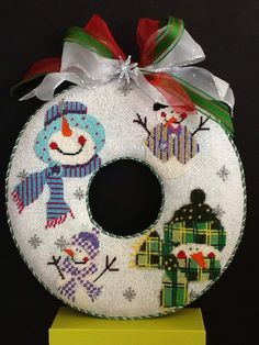 Renaissance needlepoint snowman wreath stitched by Lamb. Looks great hanging on the door.