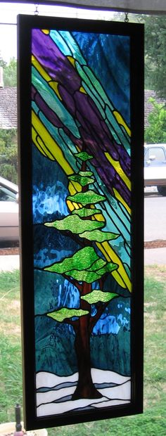 Stained glass Northern Lights and a pine tree