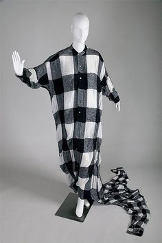 Comme des Garçons    Convertible dress/gown, c. 1992  Checked cotton/wool/nylon blend    Despite a lack of formal training in fashion design, Rei Kawakubo revolutionized fashion in the 1980s. Her company, Comme des Garçons, is credited with launching the vogue for avant garde Japanese fashion.    Comme des Garçons designs often push the limits of acceptable dress. This convertible garment is made of two separate pieces joined at the hem—a floor-length buttoned shirt and a short jacket that…