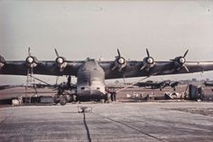 """Messerschmitt Me 323D """"Gigant"""" (Giant) heavy transport at rest in an unknown airfield in 1943. Aircraft in the background appeared to be Heinkel He 111 medium bombers. The first unit equipped with the Me 323 and formed during November 1942 was I./KG.zbV (I.Gruppe / Kampfgeschwader zur besonderen Verwendung) that had nine aircraft, and became operational in the Middle East, where a second unit II./KG.zbV 323 was formed in March 1943"""