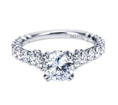 This lovely piece is an 18k White Gold Contemporary Straight Engagement Ring by Gabriel & Co.! We love how the diamonds on the sides are perfectly symmetrical leading up to the most gorgeous diamond center stone.