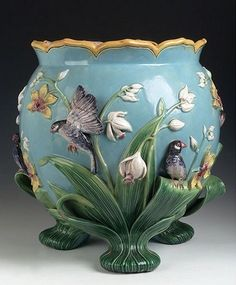 An English Victorian Majolica jardinière, in the Aesthetic taste, the yellow glazed Scalloped top with pale purple interior, the deep relief decorated sides depicting daffodils, tulips and birds on three bold leaf cast feet, each foot with impressed Victorian registration mark.
