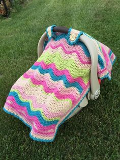 The Crochet Ripple Car Seat Cover is a baby crochet blanket that features fasteners that attach to the handle of a car seat, turning your baby blanket into a crochet canopy for your baby. When you're carrying your little baby from the car to the house or into a store, and you need to protect him or her from the rain or super bright sunshine or a harsh wind, you'll be so happy you have this crochet baby blanket. This easy ripple pattern can be quickly customized by switching ou...