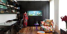 Esse home office ganhou um toque de cor com a mesinha roxa, poltrona e pufe coloridos, e um toque descontraído com o aquário colocado no painel de madeira. Projeto do designer de interiores Marco Aurélio Viterbo.
