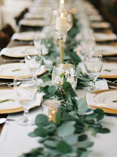 Thrifted candlesticks made from mixed metals were combined with greenery for a striking centerpiece at this celebration.