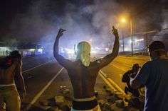 Demonstrators face off with police after tear gas was fired at protesters reacting to the shooting of Michael Brown in Ferguson, Missouri on...