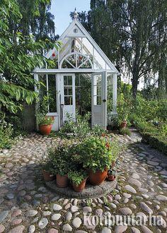 Kasvihuone on voi olla näyttävä elementti puutarhassa. Eteen ladottu mukulakivipinta korostaa kasvihuoneen tärkeyttä ja kauneutta puutarhassa. www.kotipuutarha.fi