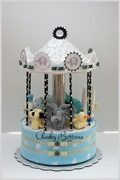 """This """"Elephant & Friends"""" Carousel was featured at an former colleague's baby shower over the weekend. Completely diaper-less, this gift is actually created with a round hat box that is hiding a few goodies for the parents-to-be (wet bag, body suit and flannel re-usable wipes). In addition, it includes one baby receiving blanket, 8 baby washcloths (three elephants, one puppy and one duck!), 2 baby spoons, 3 baby Live Clean products and 1 pair of baby booties."""
