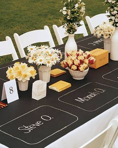 I like this idea for a banquet table: cover it with black construction paper and then chalk on place-settings and namecards for all the guests.
