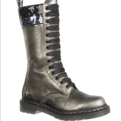 Dr. Martens Le Sequin Tall Boot Dark grey silver metallic leather with rows of silver and black sequins along the upper boot shaft. Dr. Martens® sequin cross logo on outer heel. In near perfect condition with minimal scuffing. Last photo shows largest scuff. 14 eyelet lacing. Dr. Martens Shoes Lace Up Boots