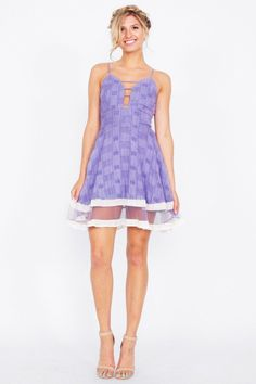 Light purple fit and flare spaghetti strap dress with cutouts in the front and a mesh inset on the hem. Lace up detail in the back. Zipper closure