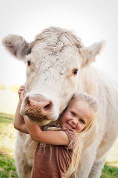Happy Farmer's Granddaughter cuddling the Cow in the Farm Field