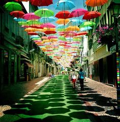 Hundreds of Floating Umbrellas Above a Street in Águeda, Portugal. If you come to Águeda, a municipality in Portugal, during the month of July, you may see hundreds of colorful umbrellas floating above some streets. They are hung over promenades giving pedestrians a nice shade and something cool to look at