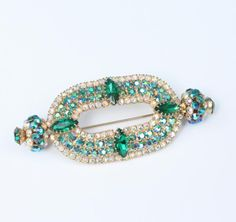 Gorgeous vintage brooch made with green rhinestones and ab rhinestone accents in an open oval with knobx of rhinestones on each end. A very unusual design, great for that holiday or special occasion. Unsigned, but with a designe...