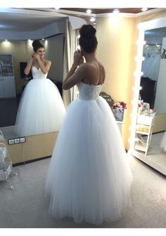 This absolutely gorgeous ball gown features a crystal-studded laced bodice with a sweetheart neckline. A classic tulle ball skirt finishes the stunning look.