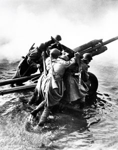 World War II, in Russia – the Great Patriotic War (22 June 1941 – 9 May 1945). Russian artillerymen transport 76-mm divisional gun ZiS-3 during the forced crossing of the Oder River. Photo by Dmitry Baltermants. Germany, December, 1944.