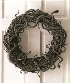 Snake Wreath. Glue dollar store snakes to a grapevine wreath and paint black. Decorate more if you wish. I think I may do one this year. Wonder if Melody wants one???