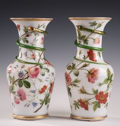 An important baluster shaped pair of vases in white enamel opaline, decorated with red, blue flowers and a snake winding up around the high collar. The collar and the base...