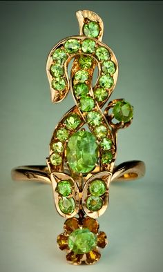A Vintage Art Nouveau Flower Ring  The long rose gold ring is modeled as a stylized Art Nouveau flower embellished with 29 sparkling green Russian Ural demantoid garnets.  The ring was made in Moscow between 1908 and 1917.  Height - 33 mm (1 1/4 in.)