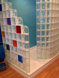 Light blue high gloss wall panels look like back painted glass are used for the 2 back wall surrounds of this colored glass block walk in shower | Innovate Building Solutions