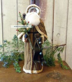 A Primitive Santa in Brown with a Feather Tree and Sleigh Bells.
