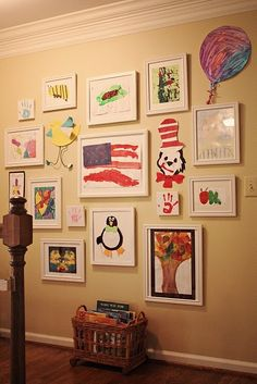Gallery wall of kid's art. Love the hand prints on 6x6 canvases..