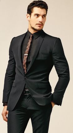 Tailored black on black; accent color skinny tie; tie bar