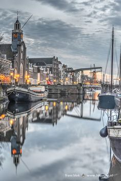 It's a quiet evening in December in Delfshaven, a part of Rotterdam that survived the 1940 bombing. Buildings and ships reflect in Voorhaven, one of the two canals of this picturesque area.