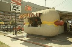 """LOS ANGELES - BEVERLY GROVE:  Tail o' the Pup was an iconic Los Angeles hot dog stand actually shaped like a hot dog. Built in 1946, the small, walk-up stand has been noted as a prime example of """"mimetic""""-type novelty architecture. It was one of the very last surviving mid-20th century buildings that were built in the shapes of the products they sold."""
