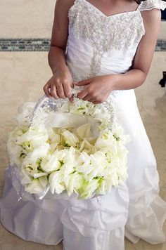 A flower girl in a white beaded dress carries a basket decorated with white roses and filled with petals.