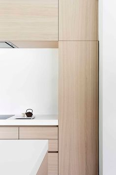 In this modern light wood and white kitchen, the cabinets are mostly free of hardware. Recessed grooves on the sides of cabinets contribute to the overall clean and minimalist feel while keeping it fully functional and easy to maneuver.