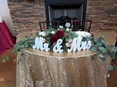 With eucalyptus draping over sides and flowers tucked in for sweetheart wedding table decor