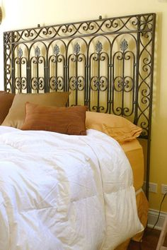An iron gate reused as a headboard, created by Kramer Design Studio