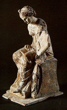 Terracotta figure of  seated young women holding a Iyre,possibly a Muse,from Tanagra,dating from the 4th century. Canellopoulos Museum  Greece