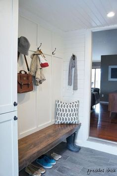 Board and batten mudroom with gray tile.