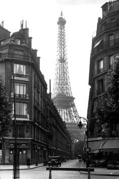 The Eiffel Tower is shown peeking between the Parisian back streets. 24 Vintage Pictures Of Paris Life In The 1920s
