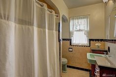 nice tile and like the semi enclosed toilet space. green sink and toilet are nice too. 1931 Tudor in West Seattle